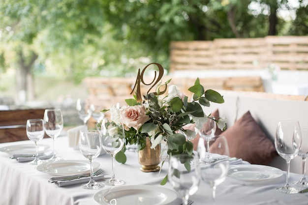 Regolazione della tabella di cerimonia nuziale decorata con i fiori freschi in un vaso d'ottone.