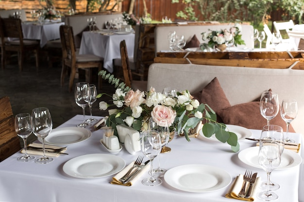 Regolazione della tabella di cerimonia nuziale decorata con i fiori freschi. tavolo per banchetti all'aperto per gli ospiti con vista sulla natura