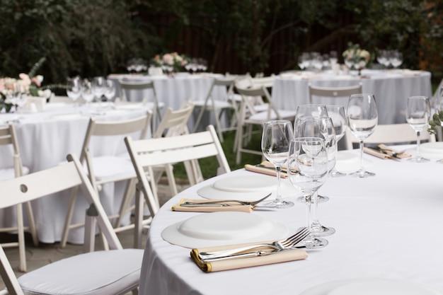 Regolazione della tabella di cerimonia nuziale decorata. tavolo per banchetti all'aperto per gli ospiti con vista sul verde
