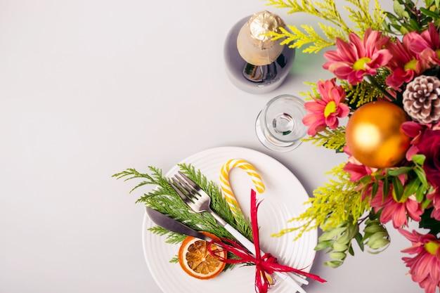 Regolazione della tabella di natale di festa con il mazzo di inverno e la decorazione naturale