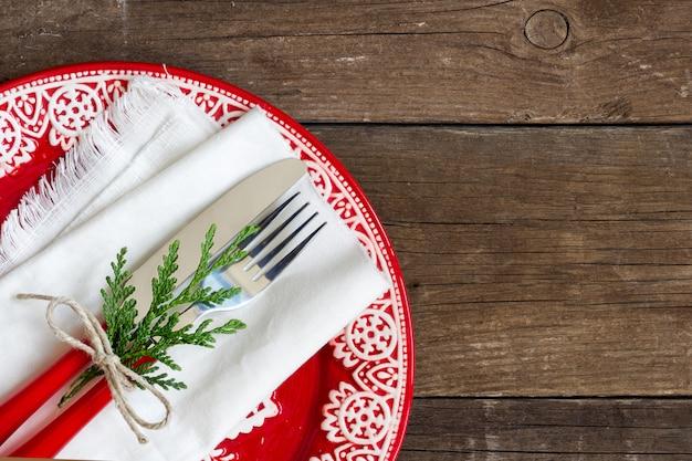 Regolazione della tabella di natale - vista superiore rossa del piatto, del tovagliolo bianco e della forcella e della lama su una tabella di legno