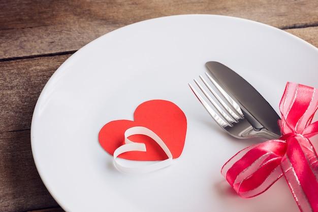 Regolazione della tavola di giorno di biglietti di s. valentino con il piatto, coltello, forcella, nastro rosso e cuori sulla tavola di legno