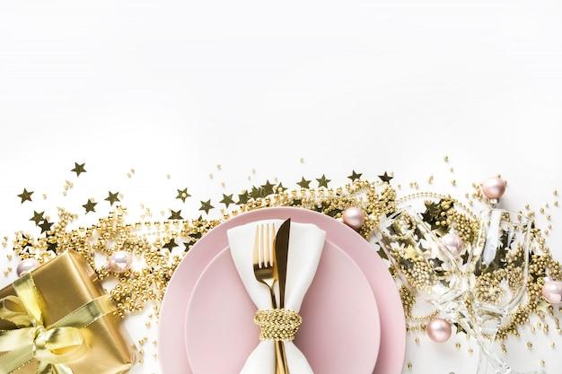 Regolazione della tavola di natale con le stoviglie rosa, argenteria dorata su bianco. vista dall'alto.