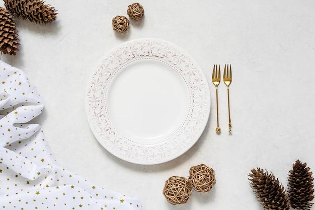 Regolazione della tavola di natale con piatto vintage bianco, forchette decorative dorate e decorazioni sul tavolo di marmo bianco