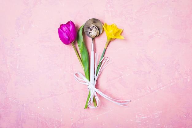 Regolazione della tavola di pasqua della primavera con i fiori e l'uovo