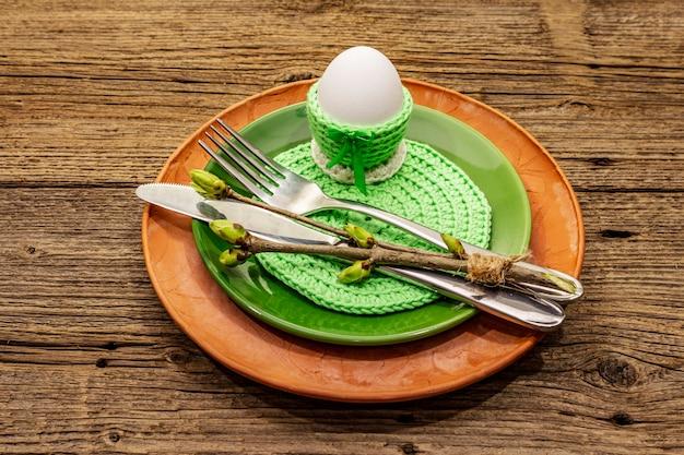 Regolazione della tavola di pasqua sul fondo di legno antico. modello di carta vacanze di primavera. posate, tovagliolo all'uncinetto, uovo, rametti di lillà