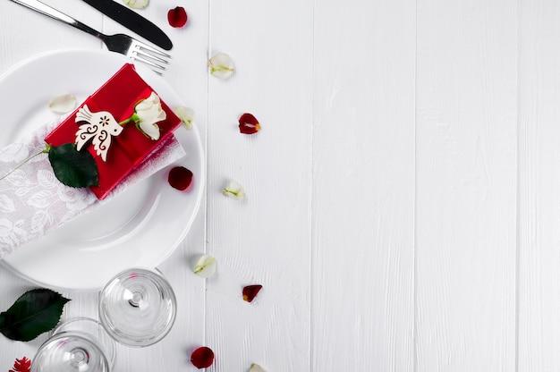 Regolazione elegante della tavola di festa con il regalo del nastro rosso