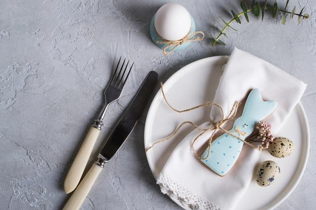 Regolazione festiva della tavola di pasqua con i biscotti del coniglietto di pasqua, le uova di quaglia e l'uovo di pollo, rametti verdi della foglia di eucalyptus. . decorazioni per le feste.