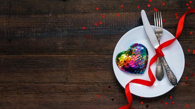 Regolazione festiva della tavola di san valentino con il cuore dell'arcobaleno sul piatto bianco e sui nastri rossi