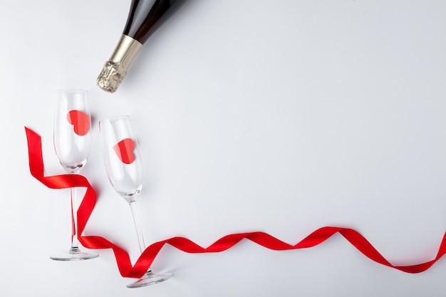 Regolazione festiva romantica della cena di san valentino, burocrazia, bicchiere di vino del champagne, bottiglia, cuori su fondo di legno bianco. copia spazio, posto per il testo. vista dall'alto.