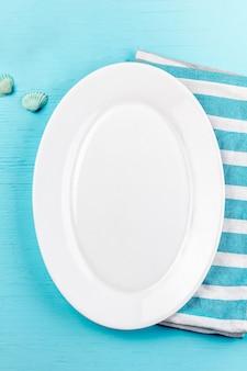 Regolazione marina della tavola con le coperture bianche delle decorazioni del mare e del piatto su fondo blu di legno