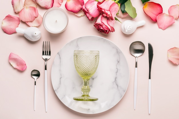 Regolazione romantica della tavola nei colori rosa. stoviglie e decorazioni per servire un tavolo festivo