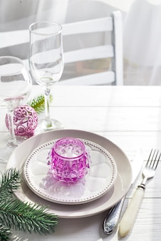 Regolazione viola della tabella di natale con il candeliere e bicchieri di vino sopra la finestra chiara