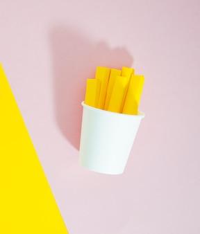 Replica di patatine fritte su sfondo rosa