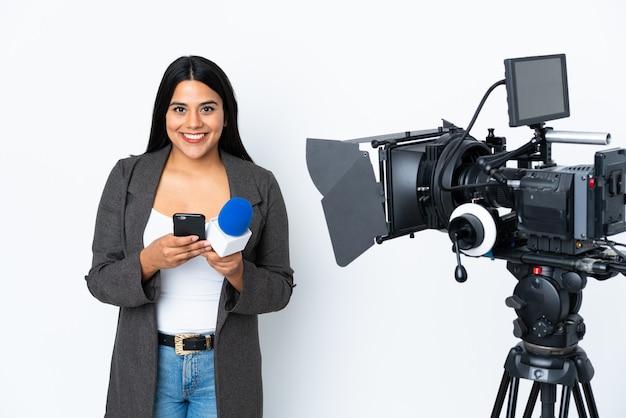 Reporter donna colombiana in possesso di un microfono e riferire notizie sul muro bianco inviando un messaggio con il cellulare
