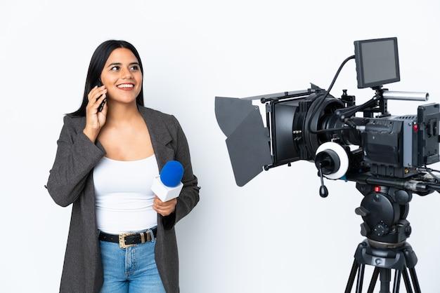 Reporter donna colombiana in possesso di un microfono e riferire notizie sul muro bianco mantenendo una conversazione con il telefono cellulare