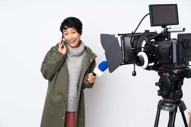 Reporter donna vietnamita in possesso di un microfono e riferire notizie mantenendo una conversazione con il telefono cellulare con qualcuno