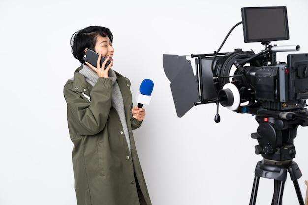 Reporter donna vietnamita in possesso di un microfono e riferire notizie mantenendo una conversazione con il telefono cellulare