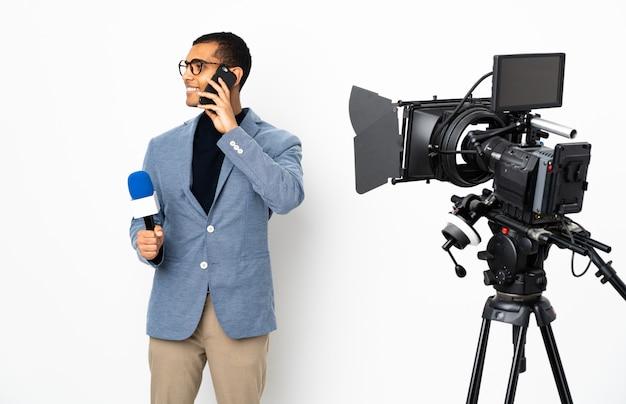 Reporter uomo afroamericano in possesso di un microfono e riferire notizie su muro bianco isolato mantenendo una conversazione con il telefono cellulare con qualcuno