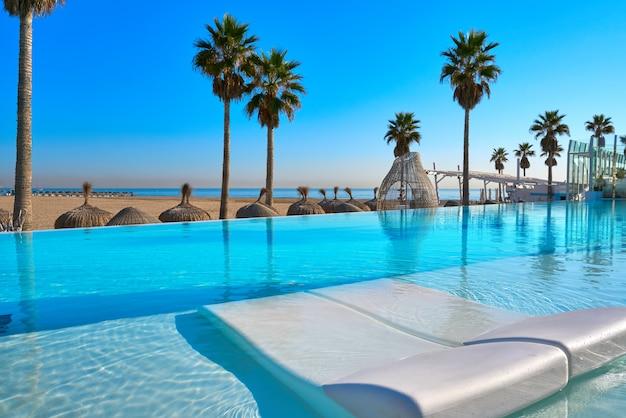 Resort piscina a sfioro in una spiaggia con palme