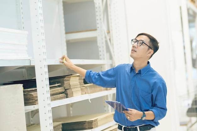 Responsabile asiatico che fa i prodotti di inventario in scatola di cartone sugli scaffali in magazzino facendo uso della compressa e della penna digitali. assistente professionale maschio che controlla azione in fabbrica.