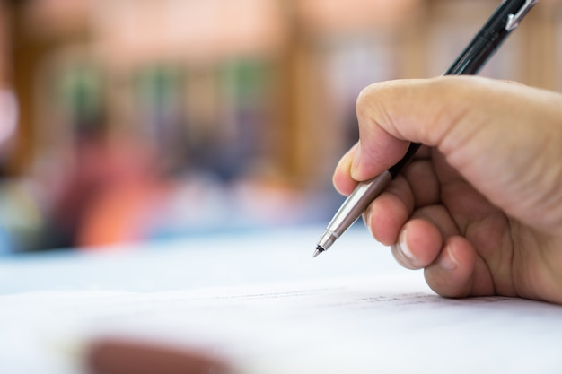 Responsabile asiatico dell'uomo di affari che controlla e che firma il candidato che riempie i documenti di documenti di rapporto