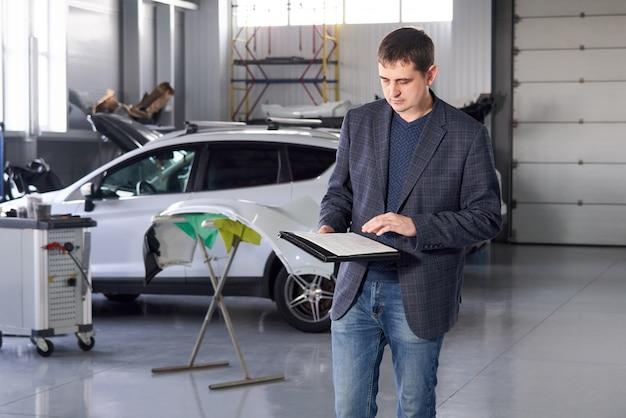 Responsabile che lavora nell'officina riparazioni automatica con un'automobile