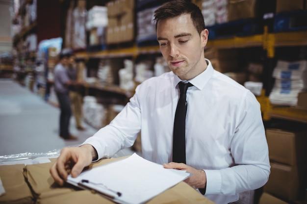 Responsabile del magazzino che esamina lavagna per appunti sulle scatole