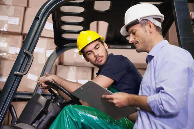 Responsabile del magazzino che parla con il driver del carrello elevatore