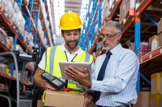 Responsabile del magazzino con il lavoratore maschio interagente sopra la compressa digitale