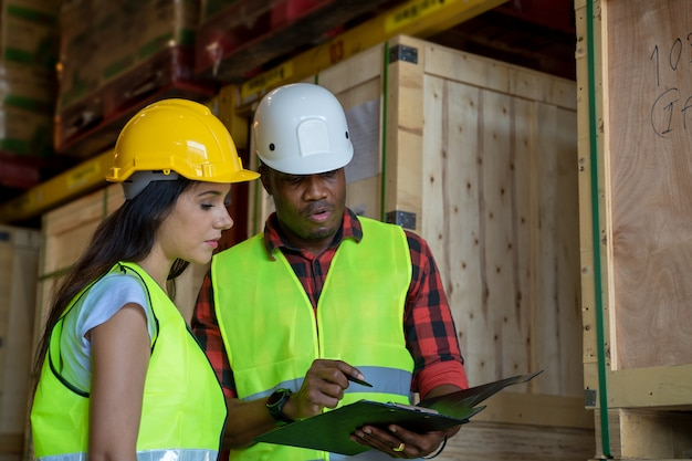 Responsabile del magazzino e casco d'uso del lavoratore del magazzino con la lavagna per appunti che controllano i prodotti circa il programma di consegna nel magazzino industriale.