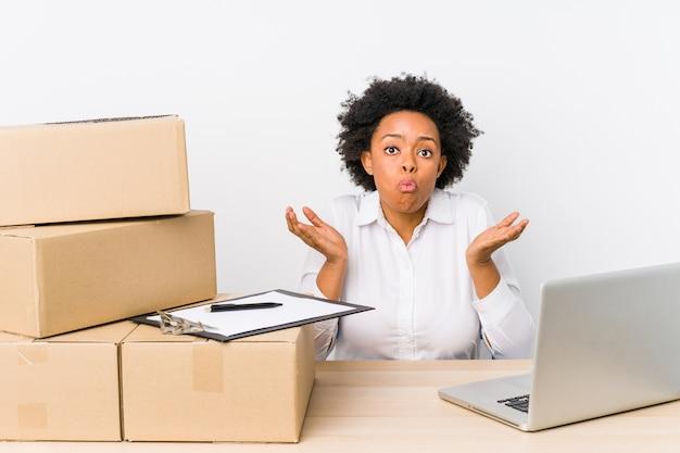 Responsabile del magazzino seduto a controllare le consegne con il laptop alza le spalle e gli occhi aperti confusi.