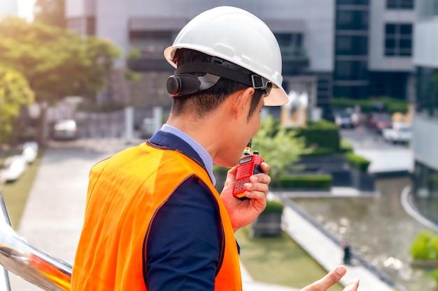 Responsabile della costruzione asiatico maschio con l'utilizzo del walkie-talkie al cantiere.