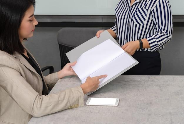 Responsabile della donna di affari che legge i rapporti e che discute con il collega per il piano aziendale di vendita. scartoffie e concetto di business