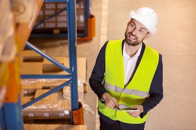 Responsabile della logistica intelligente che utilizza un tablet mentre fa il suo lavoro in magazzino