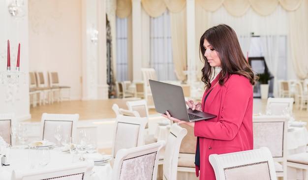 Responsabile di eventi che utilizza computer portatile nella sala per banchetti