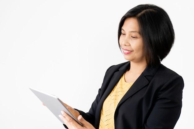 Responsabile di ufficio asiatico della donna holding business tablet che sorride e felice