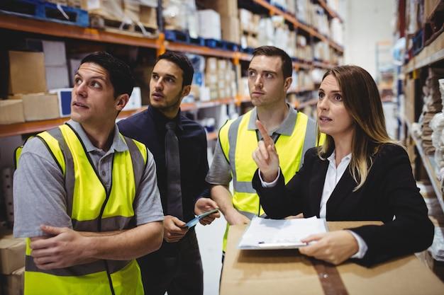 Responsabile e lavoratori del magazzino che parlano nel magazzino