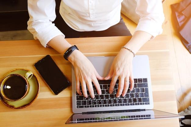Responsabile femminile dell'imprenditore che utilizza il suo computer portatile, lavorando in un caffè o in un ufficio. vicino al telefono cellulare e al caffè. posto di lavoro indipendente, colazione signora d'affari. cerca informazioni su internet.