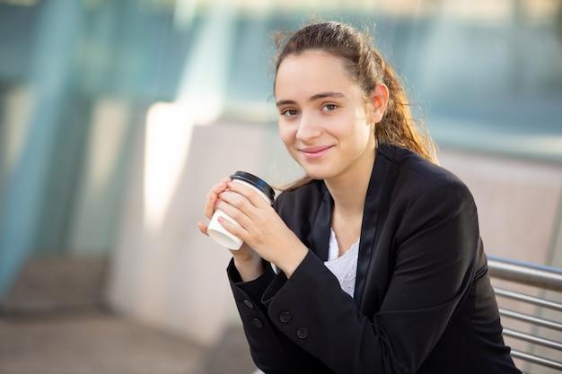 Responsabile femminile riuscito sorridente che gode dell'intervallo per il caffè