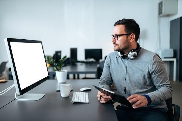 Responsabile marketing delle vendite che analizza il rapporto di dati che controlla i risultati del progetto sullo schermo del pc nel luogo di lavoro.