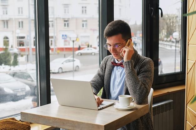 Responsabile maschio occupato che parla sul telefono cellulare e che considera orologio mentre sedendosi al computer portatile in caffè