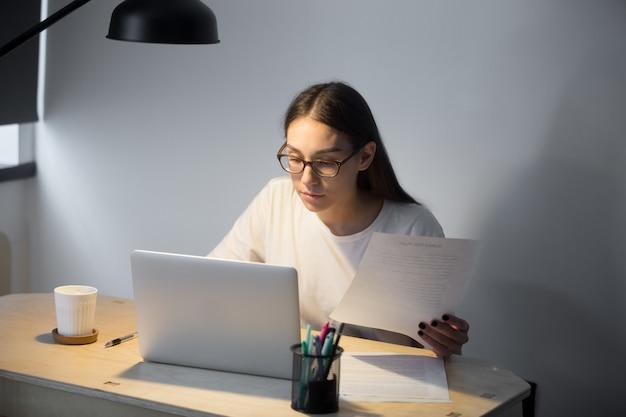 Responsabile millenario in vetri che lavora al computer portatile e che tiene documento