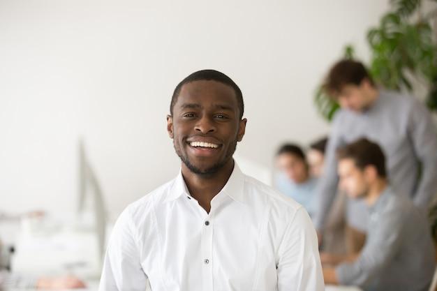 Responsabile professionale afroamericano felice che sorride esaminando macchina fotografica, ritratto di colpo in testa