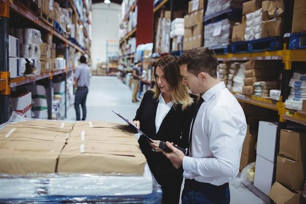 Responsabili del magazzino che esaminano lavagna per appunti in magazzino