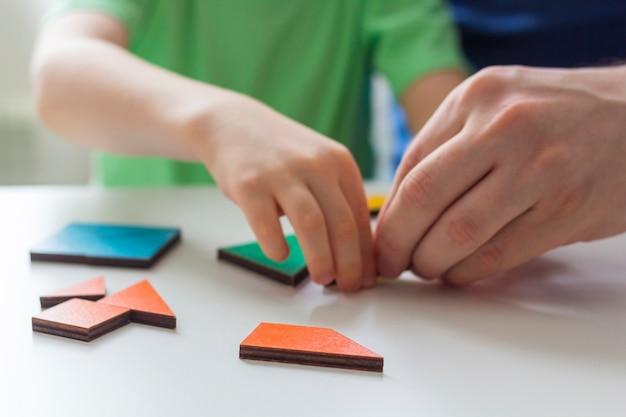 Resta a casa, distanza sociale e autoisolamento durante il concetto di quarantena. svago per la famiglia. padre e figlio giocano giochi di logica e puzzle di legno. messa a fuoco selettiva. giochi educativi per bambini