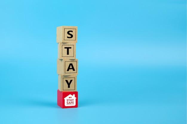 Resta a casa resta al sicuro icone sul blocco di giocattoli in legno. concetti per la salute e la prevenzione medica dell'infezione da coronavirus o covid-19.