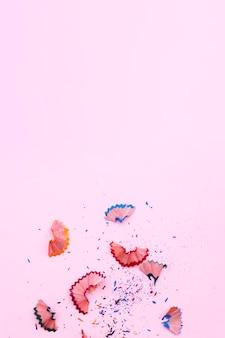Resti di matite affilate su sfondo rosa con spazio in cima