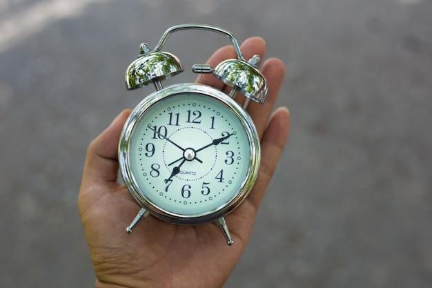 Restro classic alarm clock in a hand. il tempo è in esecuzione.