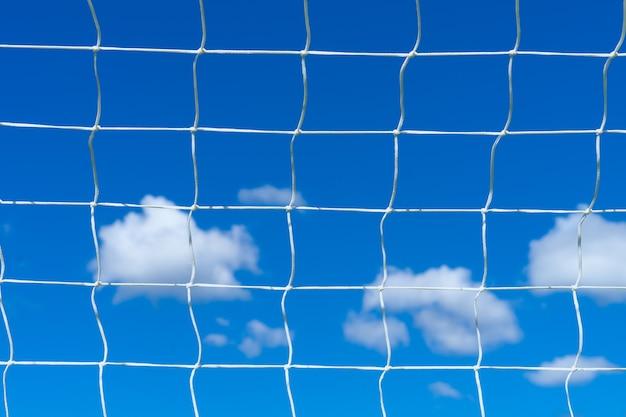 Rete da calcio con cielo azzurro e nuvole bianche